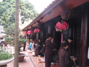 Mulheres fazendo orações na frente do pagode no templo de Tran Quoc